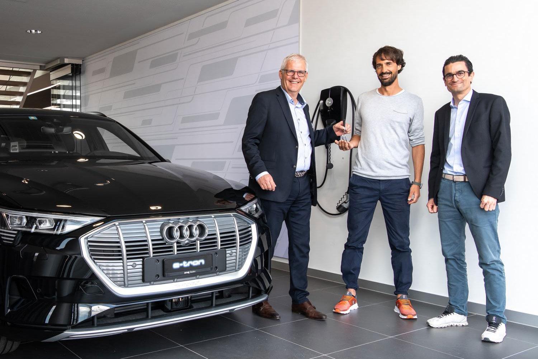 Caspar Coppetti (al centro) prende in consegna la sua nuova Audi e-tron da Thomas Huser (a sinistra), direttore di AMAG Baden, e Livio Piatti (a destra), Head of Marketing Audi Svizzera.