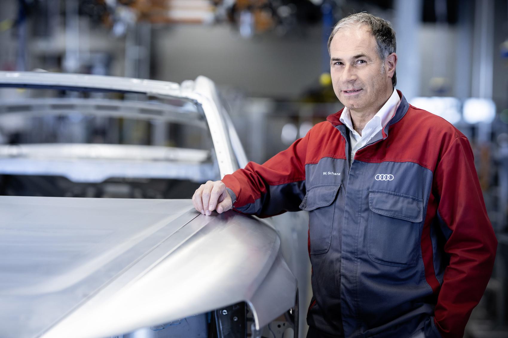 Produktionsleiter Wolfgang Schanz posiert mit einer e-tron-GT-Karosserie. (Audi)